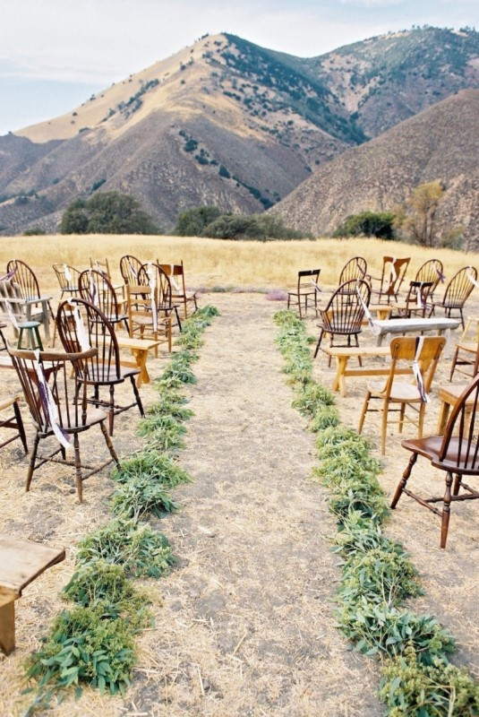 a natural and simple mountain ceremony space done with wooden chairs, greenery runners and a gorgeous mountain view
