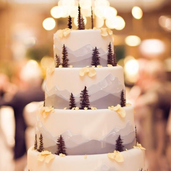 a gorgeous mountain wedding cake with little trees, blooms and petals is a cool way to embrace the location