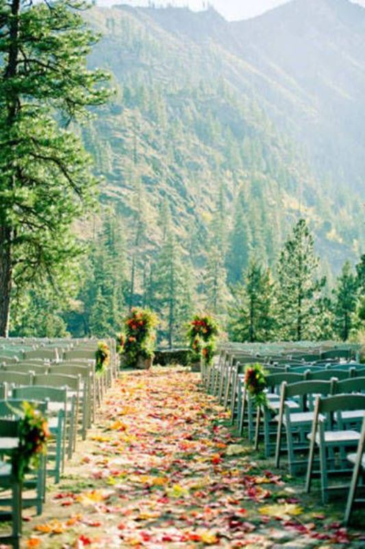 a beautiful wedding ceremony space done with colorful fall leaves and petals, greenery and a fantastic mountain view