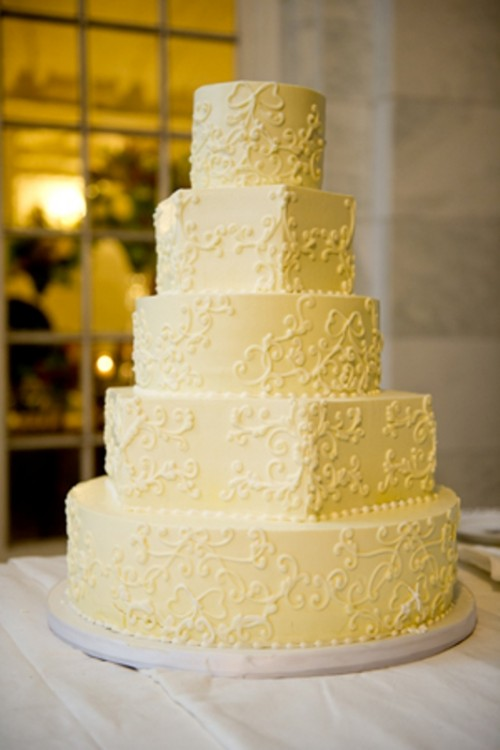 a yellow patterned wedding cake with sugar beads is a traditional and elegant wedding dessert