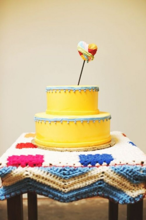a bold and cool yellow wedding cake with blue ribbons with bells and a bold yarn heart topper is a whimsy dessert idea