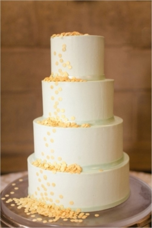 a neutral wedding cake with green ribbons and yellow polka dots is a cool and bold idea for spring or summer