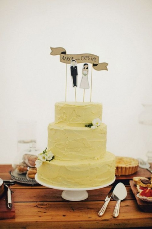a pale yellow textural wedding cake with white blooms and cake toppers, with the couple's names is a cool idea