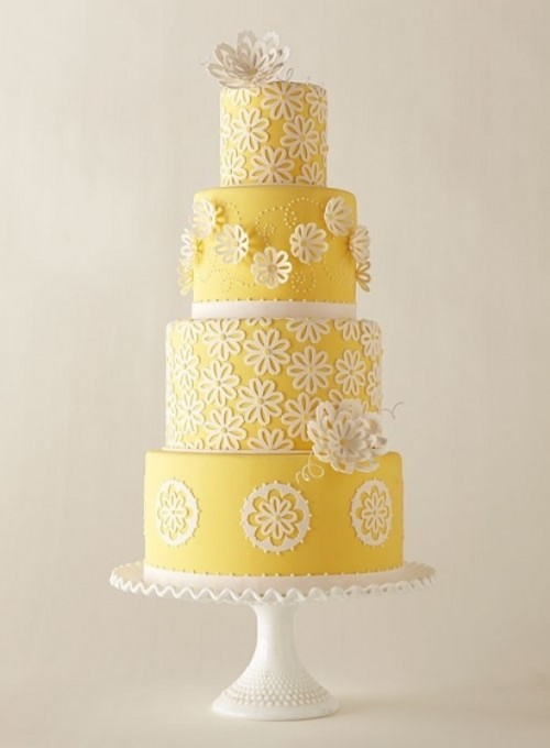 a yellow and white patterned wedding cake with sugar blooms that are dimensional and usual and a sugar bloom on top