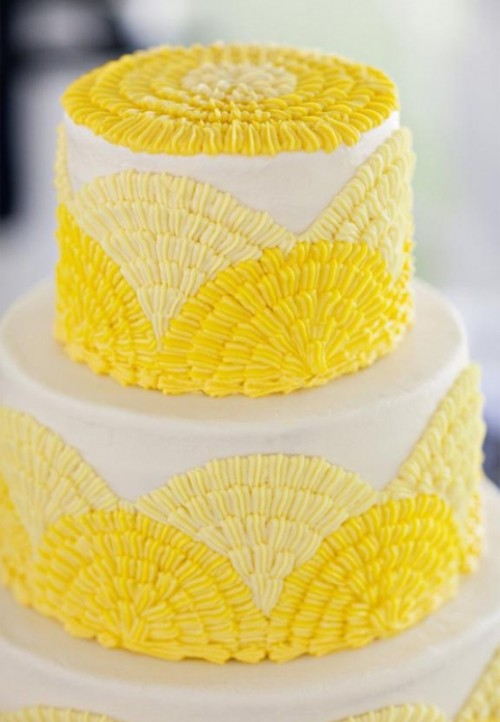 a white wedding cake with pale and bright yellow sugar patterns and some of them on top is a fun and bold idea