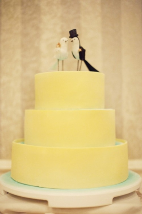 a yellow plain wedding cake with mini birds on top is a stylsh colorful idea to rock