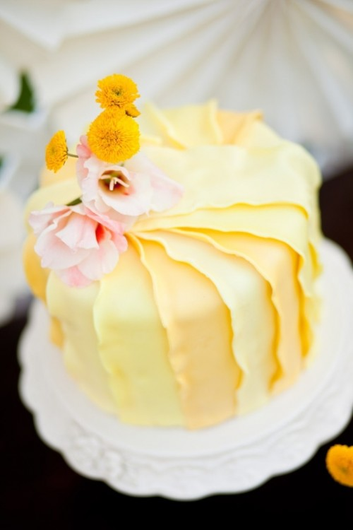 a yellow ruffled tiered wedding cake with pink and yellow blooms is a lovely and refined idea for a vintage wedding