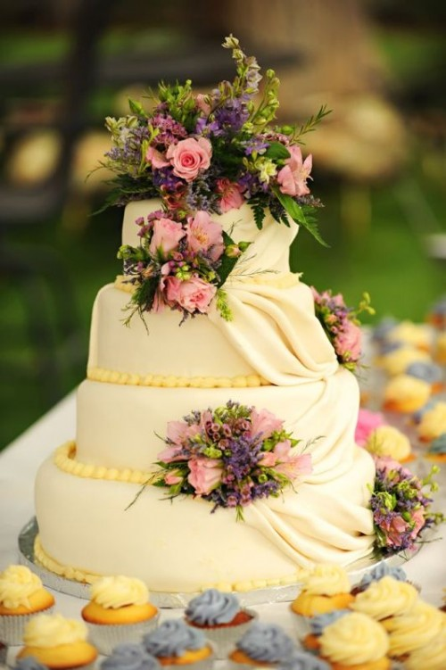 an ivory wedding cake with yellow beads and tiers of sugar, with bright fresh blooms and greenery