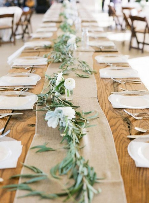 a simple wedding table runner of olive foliage and white blooms plus a burlap runner to pair it with are a cool rustic combo