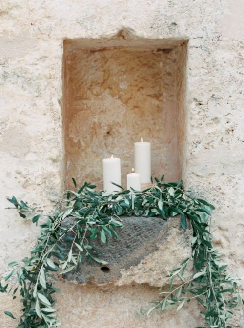 a niche decorated with olive greenery and pillar candles will give a refined yet natural feel to your space