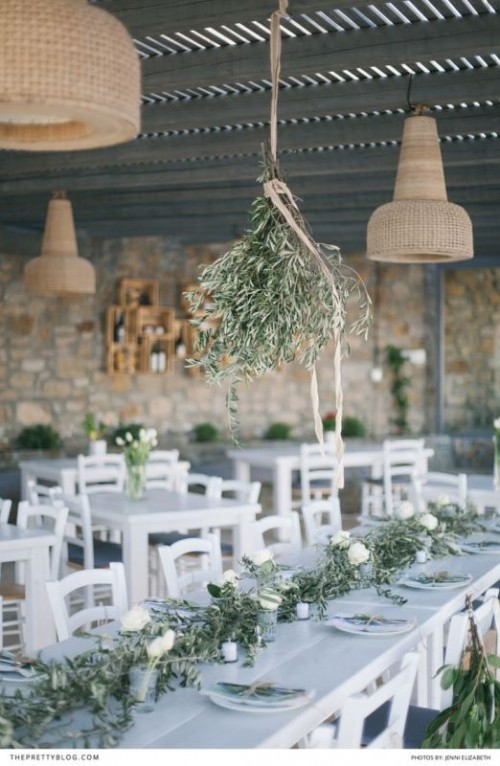 a olive greenery chandelier and matching table runners with candles and white blooms is a cool rustic setup for a wedding venue