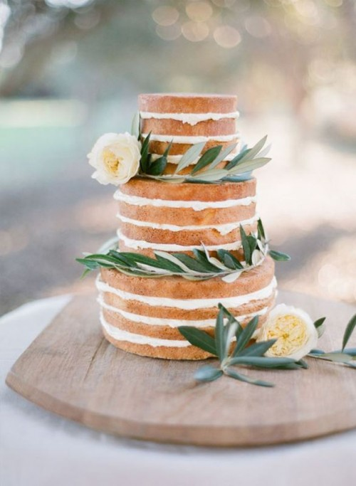 a naked wedding cake with olive greenery and white blooms is a cool idea for spring or summer weddings