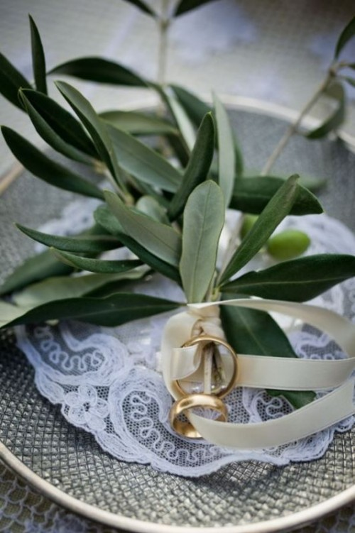 a porcelain plate with a lace doily and some olive branches to hold the rings is a cool idea for a natural wedding