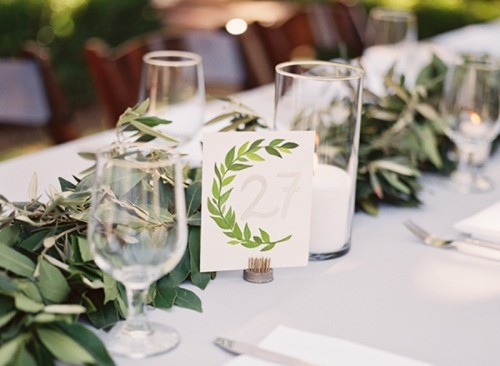 an olive greenery table runner and a matching card to decorate the wedding table in a natural way