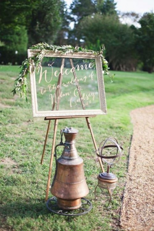 a large wedding sign of an old window and some olive branches on top is a cool idea to decorate the wedding space