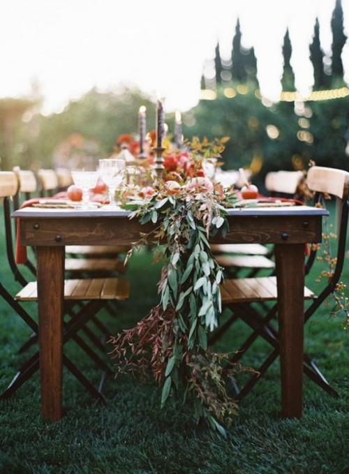 a fall wedding table runner with olive greenery, dried greenery and foliage and pomegranates and other fruits