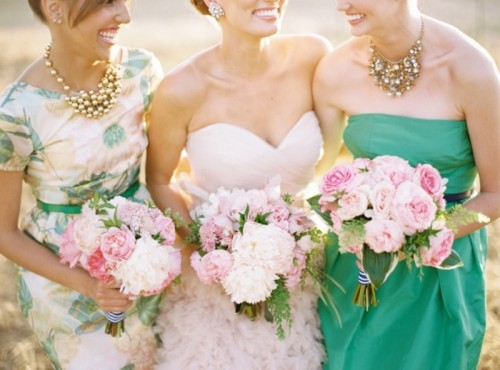 mismatched bridesmaid dresses - a blush strapless one, an emerald strapless one and a floral dress with short sleeves
