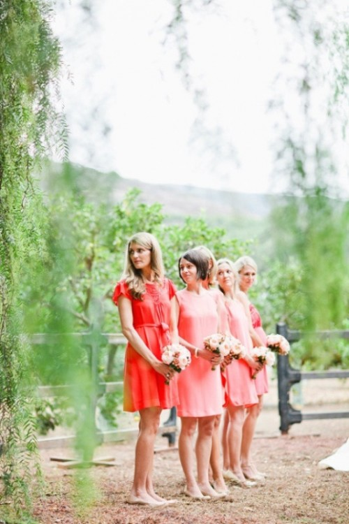 mismatched bright pink and red bridesmaid dresses plus nude heels for a stylish spring or summer wedding