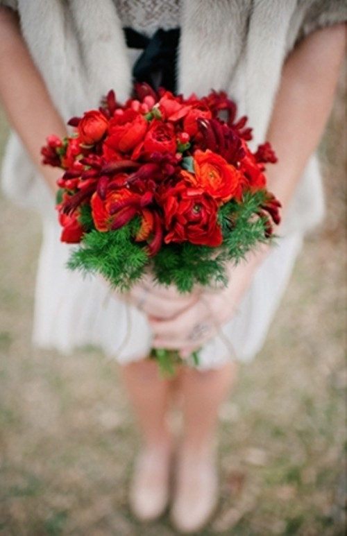a bold red flower bouquet with fir branches is a stunning piece to complete your bridal look