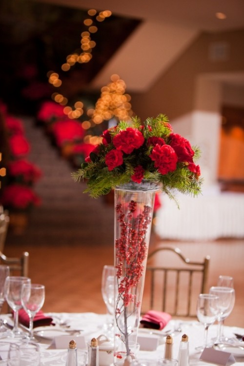 a tall vase with berries, red blooms and fir is a stylish and easy rustic centerpiece for a winter or Christmas wedding