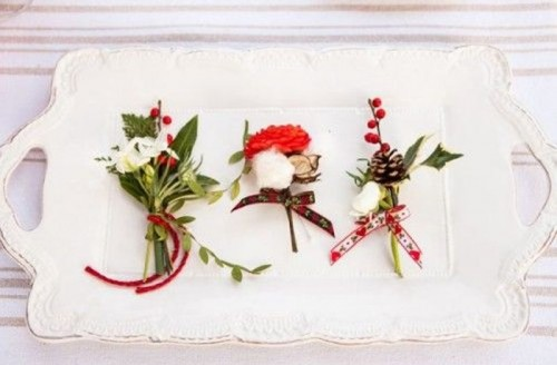 cool green, white and red boutonnieres with leaves, pinecones, cotton and wood slices and bright ribbons
