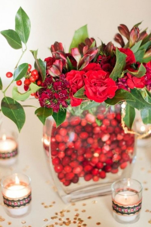 a bold winter centerpiece of a vase filled with cranberries, red blooms, leaves and berries is a perfect winter or Christmas wedding decoration you may easily make