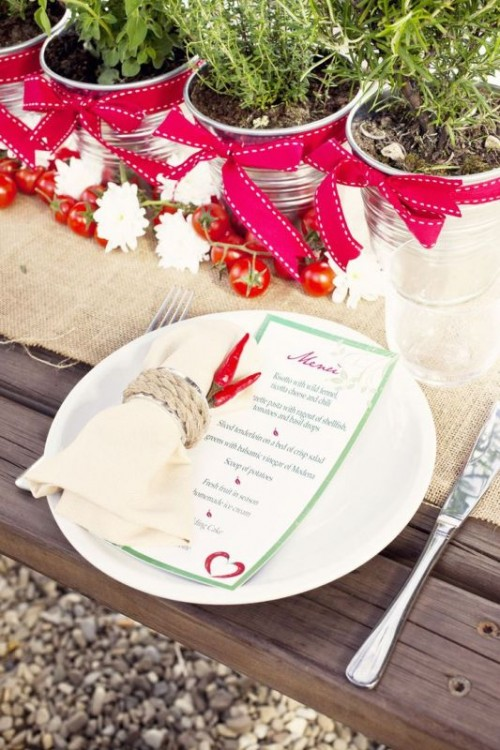 a winter or Christmas wedding tablescape dotted with red and grene touches, with potted herbs and menus and napkins