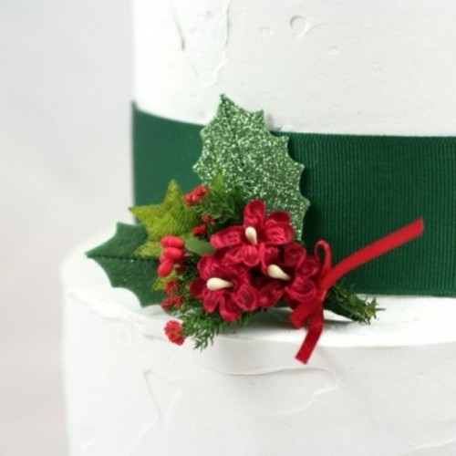 a white wedding cake with a green ribbon, green leaves and berries is a traditional idea for a winter wedding