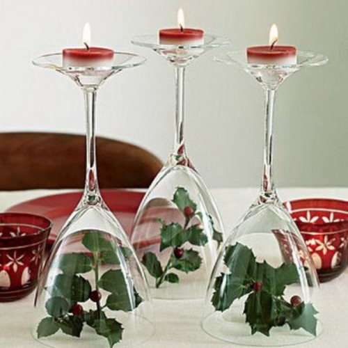 glasses with greenery, berries inside and red candles on top for decorating a winter or Christmas wedding