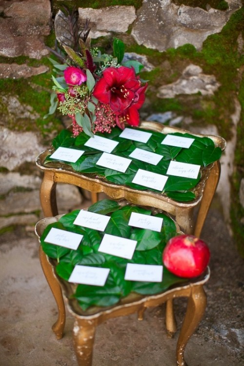 vintage wooden stools covered with leaves, cards, red blooms and a pomegranate for winter weddings