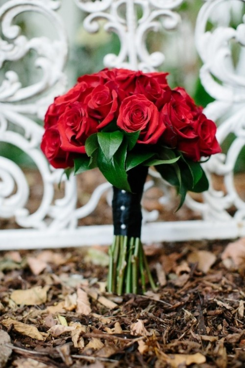 red roses, a black wrap with buttons is a chic and stylish winter wedding bouquet that never goes out of style