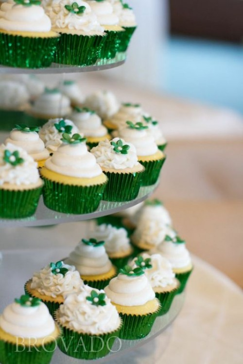 cupcakes with frosting and green sugar flowers on top plus green liners are great for a winter or Christmas wedding