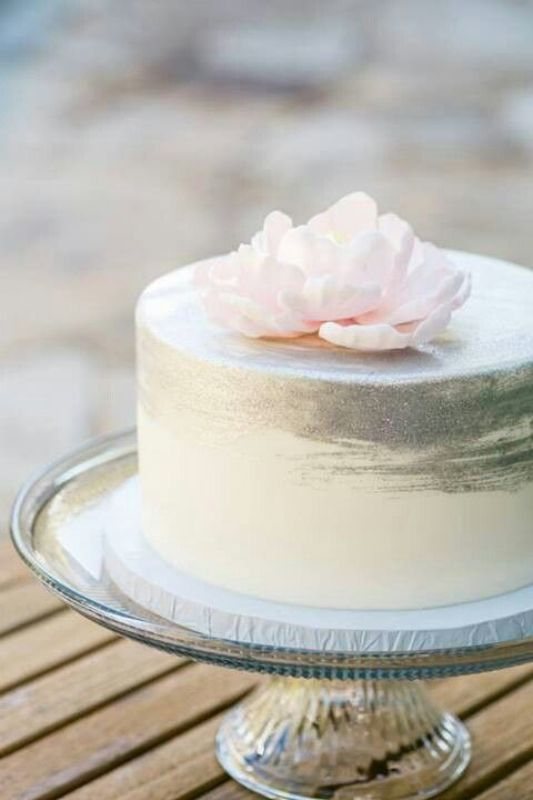 a subtle ombre white to silver one tier wedding cake topped with a pink bloom is a chic idea