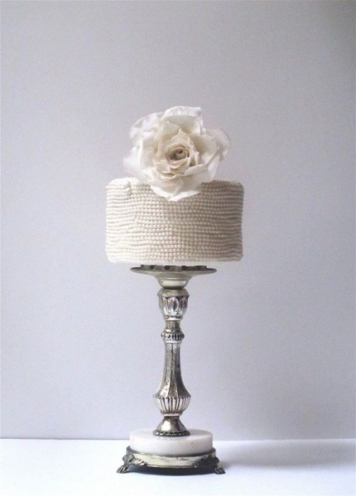 a white bead covered wedding cake topped with a large white fresh bloom is ideal for an elegant and chic wedding