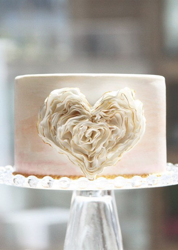 a blush watercolor wedding cake with a layered sugar heart on its side is a fresh and modern idea