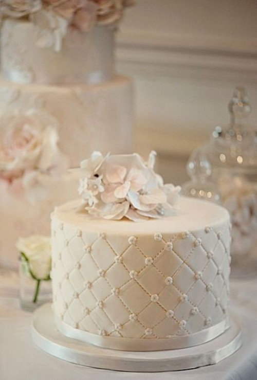a white textural wedding cake with white sugar blooms is a beautiful and elegant dessert