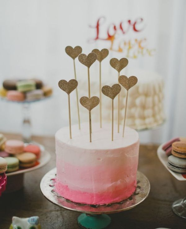 an ombre pink wedding cake with multiple glitter heart toppers is a bright and very glam idea