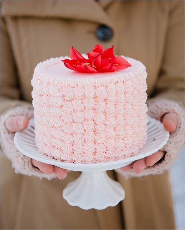 a pink buttercream onne tier wedding cake topped with bright red blooms on top is a cute idea