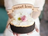 a one tier wedding cake with fresh flowers and a wooden topper is a gorgeous rustic dessert idea