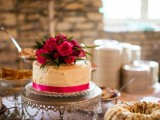 a textural one tier wedding cake with a pink ribbon and bright red flowers on top for a touch of drama