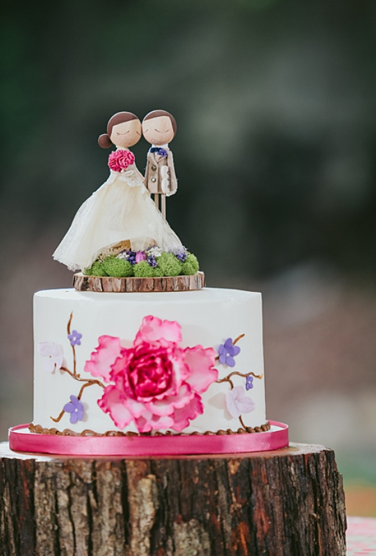 a handpainted one tier wedding cake with a fun topper on a wood slice with moss