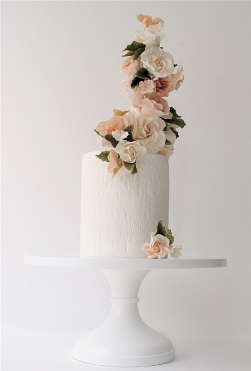 a tall textural one tier wedding cake with a tower of blush and neutral blooms on top is a very stylish idea