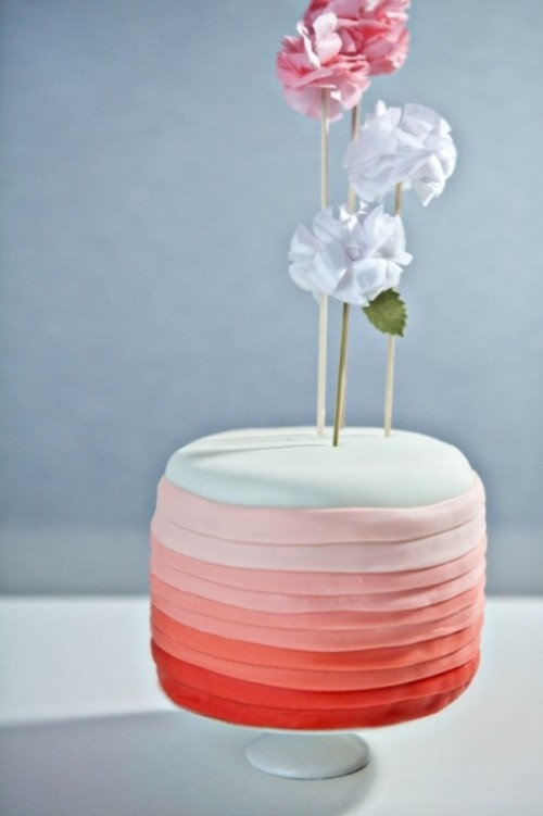 a colorful one tier wedding cake that seems to consist of multiple layers thanks to bright frosting and a cute topper