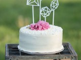 a white buttercream wedding cake topped with fresh pink blooms and with geometric toppers