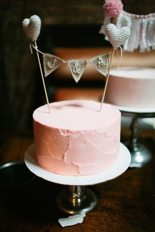 a pink textural one tier wedding cake with a burlap topper and hearts is a simple rustic idea