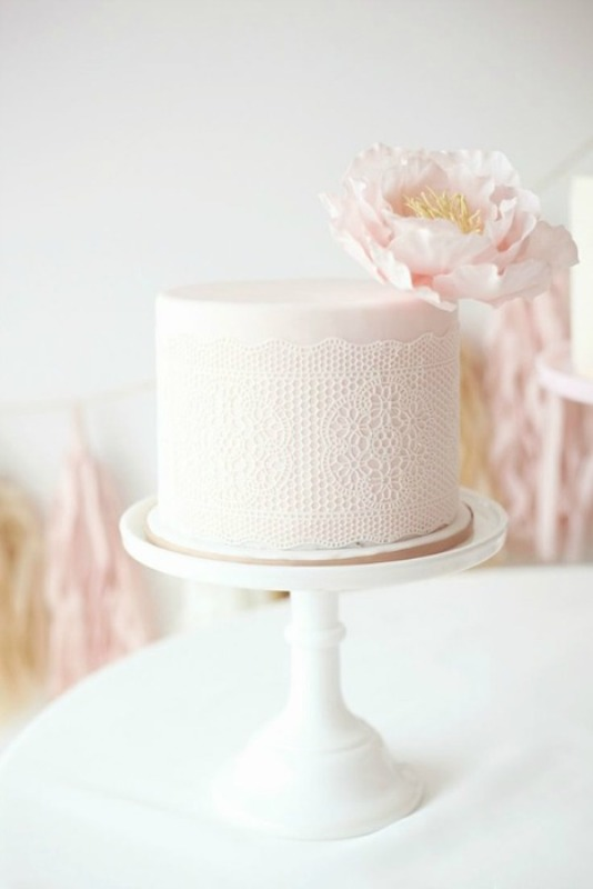 a blush wedding cake with lace decor and a single blush bloom on top is a very subtle and tender option