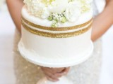 a white one tier wedding cake with gold glitter stripes and fresh neutral blooms is a very chic and elegant idea