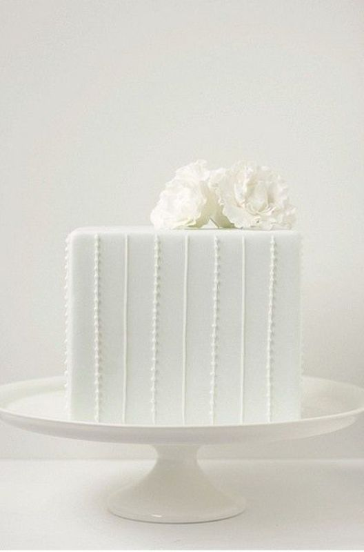 a white square wedding cake with fresh blooms on top is timeless classics for most of modern weddings