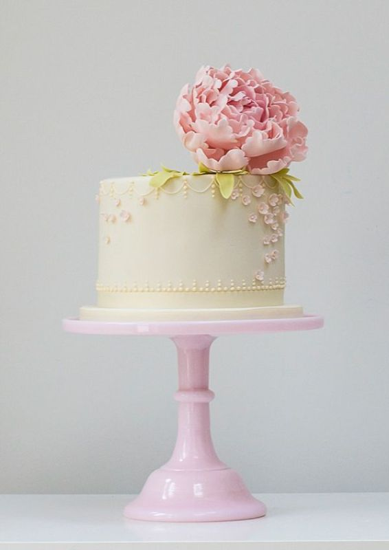 a neutral buttercream wedding cake decorated with pink sugar blooms and a fresh pink peony on top feels romance and vintage