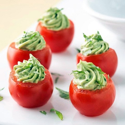 fresh tomatoes filled with greenery and cream cheese are a refreshing fall appetizer to go for